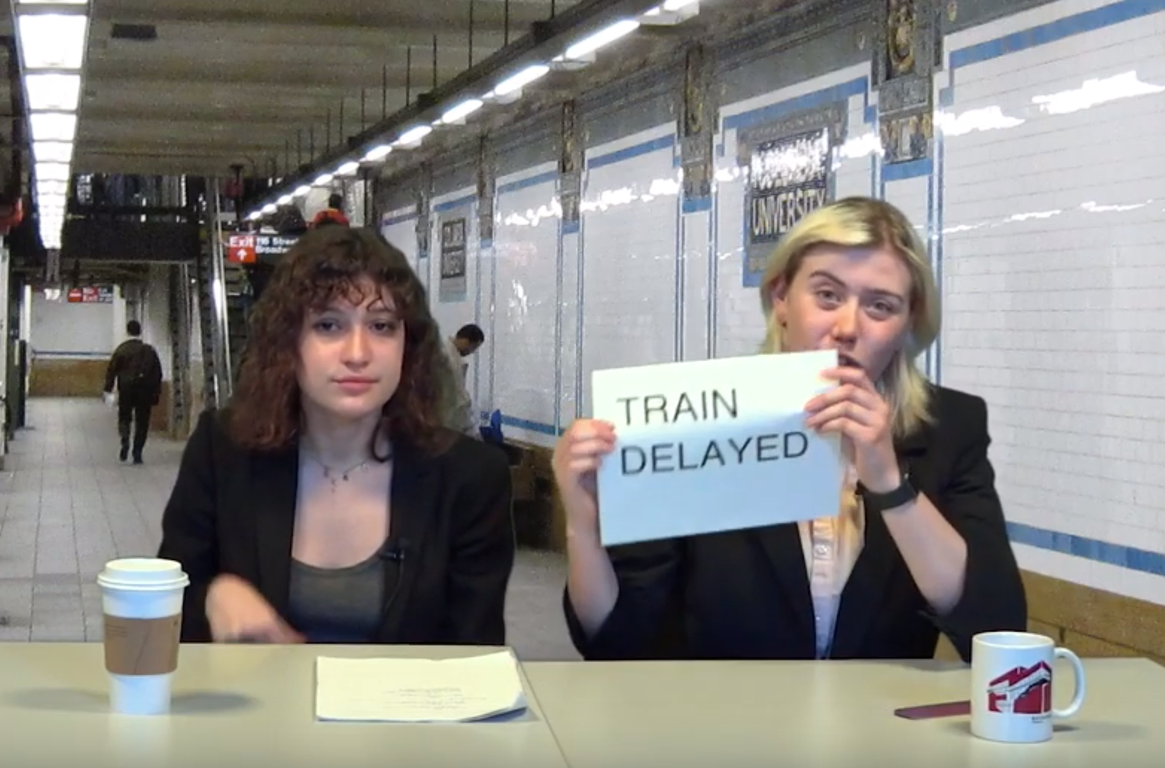 Students sitting at desk at Columbia subway station; one is holding a sign that says 'train delayed'